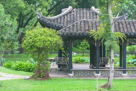 Chinese pagoda surrounded with green trees at public park.