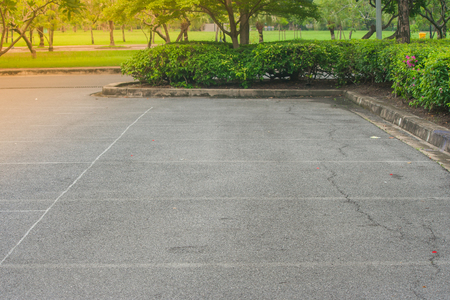 Empty space in parking lot at public park with green bush and sunlight background.