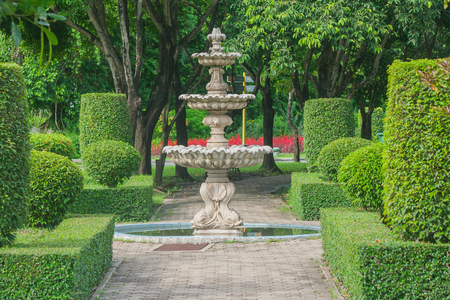 Watering fountain in public park with green natural background.