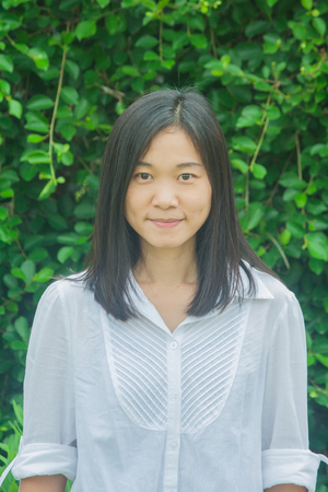Asian woman portrait wear white shirt, smiling and looking forward with green tree background. Stok Fotoğraf
