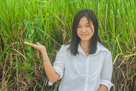 Asian woman portrait wear white shirt, holding open hand and smiling with green tree background.