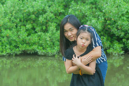 Adorable Family Concept : Asian woman and children standing on green grass, smiling and hug together at public park. Stok Fotoğraf