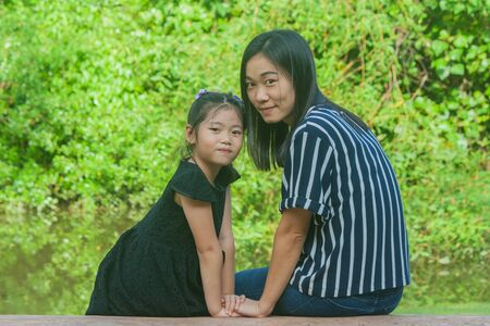 Adorable Family Concept : Asian woman and children smiling and sitting relax on concrete long bench at public park.