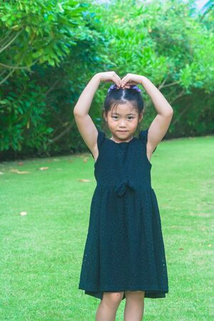 Cute little girl standing on green grass and raise up hers hand to make heart shape over head with sunlight background at public garden. Stok Fotoğraf