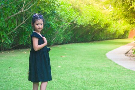 Cute little girl standing on green grass with sunlight background at public garden. Stok Fotoğraf
