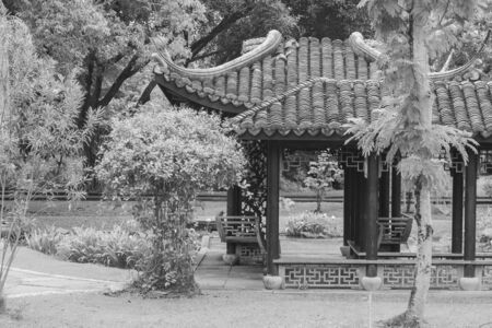 Chinese pagoda surrounded with green trees at public park. (Black and White filter effect)