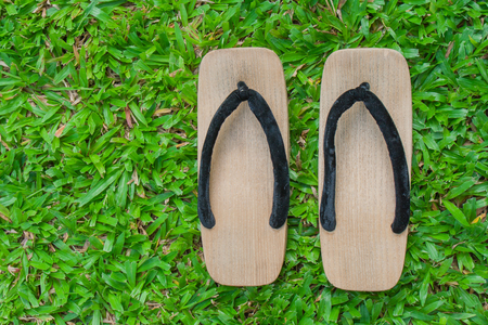 Top view close up old wooden sandal with a thick sole on green grass. Stok Fotoğraf