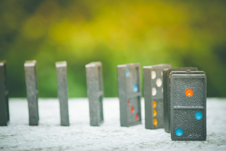 Soft Focus - Domino Effect Concept : Row of black dominoes on concrete floor and green bush with bokeh and sunlight background. (Autumn filter effect) Stok Fotoğraf