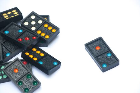 Close up black color dominoes with colorful dot pieces lie on white background. Stok Fotoğraf