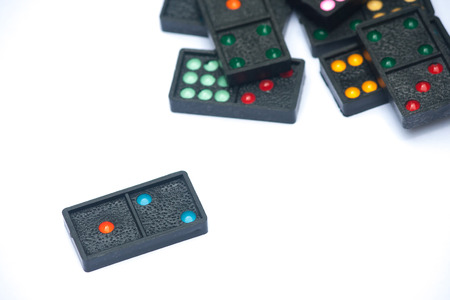 Close up black color dominoes with colorful dot pieces lie on white background. Stok Fotoğraf - 82680947