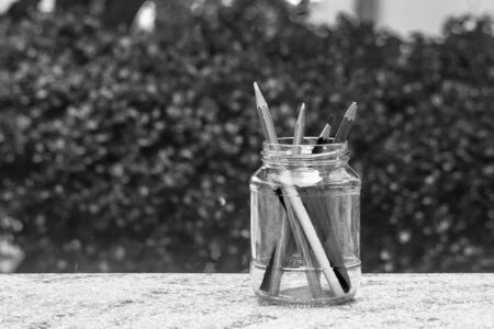 Various pencil in glass bottle on concrete floor with green bush background. (Black and White filter effect) Stok Fotoğraf