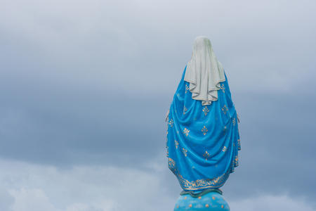 Behind view of The Blessed Virgin Mary statue standing in front of The Roman Catholic Diocese that is public place in Chanthaburi Province, Thailand. Stock Photo