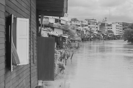 Tropical view of old waterfront home located beside river at countryside of Chanthaburi Province, Thailand. (Black and White filter effect)