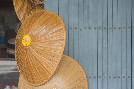 Close up bamboo weave hat hanging on metal door.