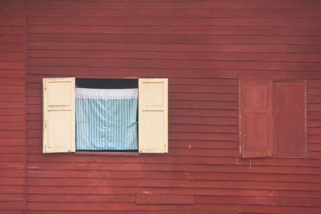 Mening van gordijn en houten venster op rode muur van blokhuis bij platteland in uitstekende stijl. Stockfoto