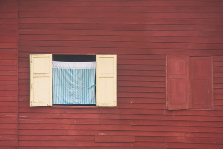 View of curtain and wooden window on red wall of wooden house at countryside in vintage style.
