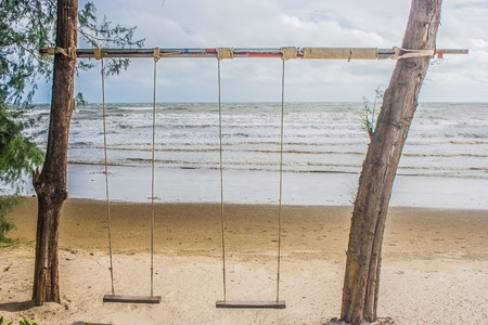 Wooden swing hanging from tree on the beach with seascape view background. (Vintage filter effect)