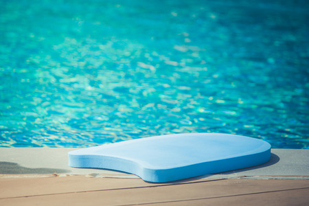 Close up swimming foam board lie on edge of swimming pool with blue water background. (Autumn filter effect)