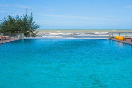 Zwembad in modern ontwerp bij hotel met overzeese mening en blauwe hemelachtergrond.