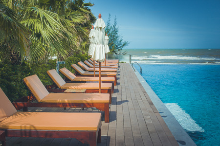 Vacation and Relaxation Concept : Daybed beside swimming pool in the resort with sea and blue sky background.