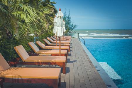 Vakantie en Ontspanning Concept: Daybed naast zwembad in de toevlucht met overzees en blauwe hemelachtergrond.