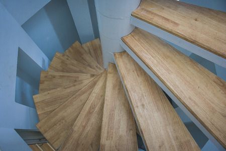 Top view of spiral wooden staircase with blue wall.