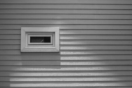Mening van houten venster op grijze muur van blokhuis bij platteland in uitstekende stijl. Stockfoto