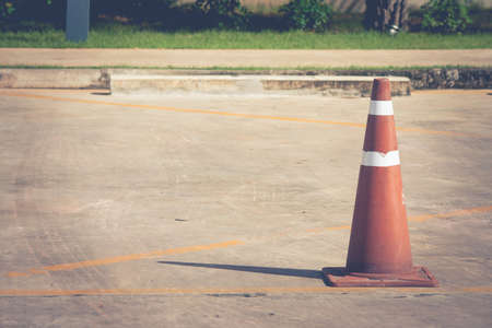 Old orange traffic cone standing on concrete floor in front of empty parking lot for reservation. (Vintage filter effect)