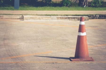 Oude oranje verkeerskegel die zich op concrete vloer voor leeg parkeerterrein voor reservering bevindt. (Vintage filtereffect)