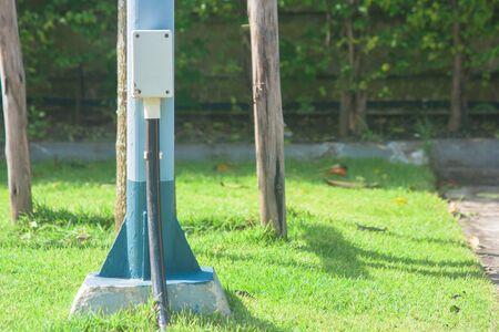 Sluit omhoog aardedraad op elektrische pool naast parkeerterrein bij buitengebouwen. Stockfoto