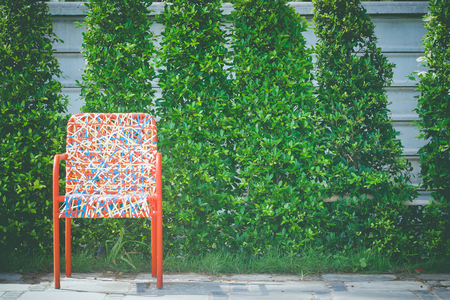 Colorful plastic weaving rattan chair standing on concrete floor with green tree. Stok Fotoğraf - 83279520