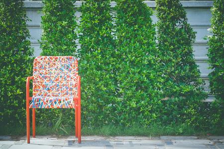 Kleurrijke plastic wevende rotanstoel die zich op concrete vloer met groene boom bevindt. Stockfoto