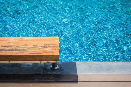 Vakantie en Ontspanning Concept: Houten lange stoel naast zwembad in de toevlucht met blauwe waterachtergrond.