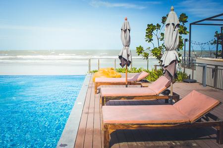 Vakantie en Ontspanning Concept: Ligbed naast zwembad in de toevlucht met overzees en blauwe hemelachtergrond. (Vintage filtereffect)