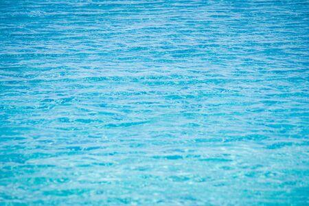 Sluit omhoog van fonkelend blauw water met golfoppervlakte in zwembad. (Selectieve focus) Stockfoto