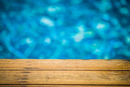 Close up wooden long chair with blue water in swimming pool background. (Selective Focus) Stok Fotoğraf