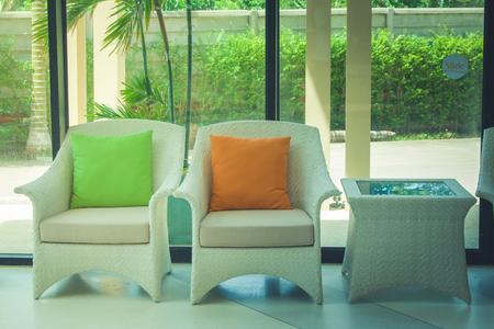 Vakantie en Ontspanning Concept: Sluit omhoog plastic wevende rotanstoel met groen en oranje hoofdkussen in hal van toevlucht. (Herfstfiltereffect)