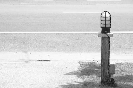 Straatlantaarn op hout met gronddraad naast gang op de weg. (Zwart en wit filtereffect) Stockfoto