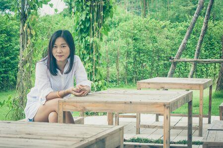 Ontspanningconcept: Vrouw het ontspannen op houten stoel bij openluchttuin omringde groene natuurlijk. (Vintage filtereffect)