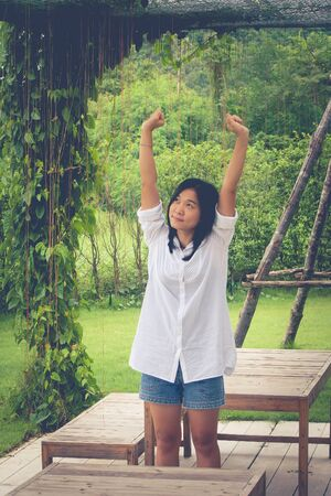 Relaxation Concept : Asian woman wear white shirt and stretch in the garden. (Vintage filter effect)