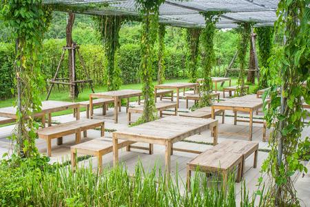 Houten stoel en tafel in een prachtige tuin in de open lucht. Stockfoto