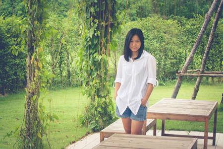 Ontspanningsconcept: Het Aziatische witte overhemd die van de vrouwenslijtage zich op gras bij openluchttuin bevinden. (Vintage filtereffect)