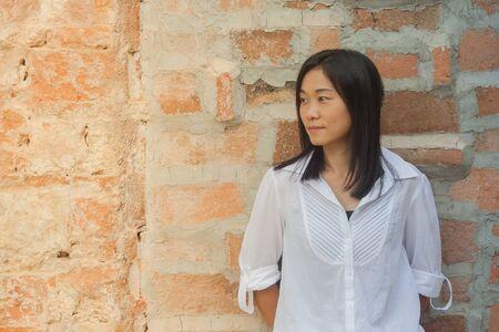 Foto schieten Aziatische vrouw portret slijtage wit overhemd en zijwaarts op zoek met rode bakstenen achtergrond (Vintage filter effect)
