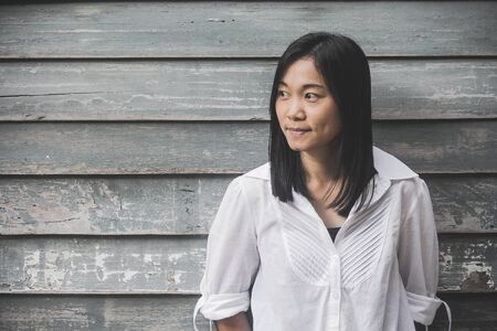 Foto schieten Aziatische vrouw portret slijtage wit overhemd en zijwaarts op zoek met houten muur achtergrond (Vintage filter effect)
