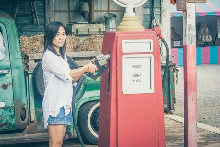 Portrait Asian woman holding red petrol pump nozzle with retro car background at countryside. (Vintage filter effect)