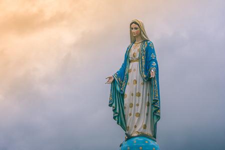 Maagdelijk Mary-standbeeld bij Katholieke kerk met zonlicht op bewolkte dagachtergrond, Chanthaburi-Provincie, Thailand.