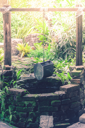 Old brick water well with bucket hanging on timber in the garden with sunlight background.