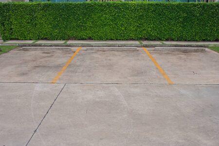 Lege ruimte in autoparkeerterrein bij openluchtpark met groene struikachtergrond. Stockfoto