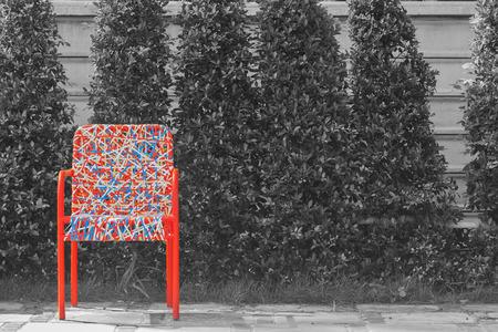 Abstracte kleurrijke plastic wevende rotanstoel die zich op concrete vloer met zwart-witte achtergrond bevindt. Stockfoto