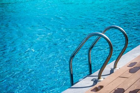 Metalen handgreep ladder in blauw water zwembad in het resort. Stockfoto